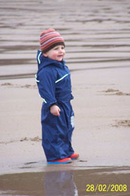 Luke snug and warm in a Puddle suit on a February day at the beach
