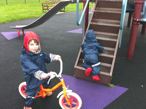 Alexander and Eliza playing in the park in Ocean Suits and Togz booties