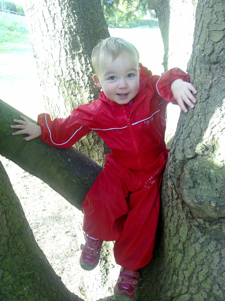 Eilidh in puddle suit in a tree