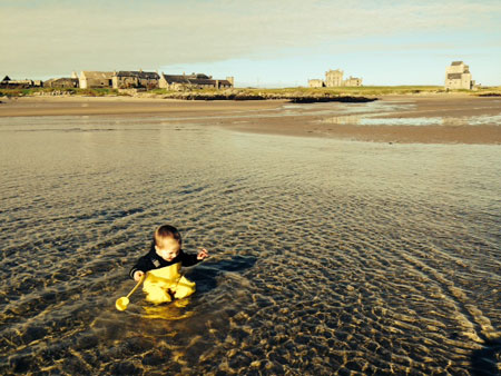 Eoghan playing on the beach in his waders