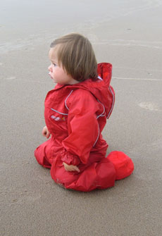 Iona enjoying the beach in her Puddle Suit and Togz Booties