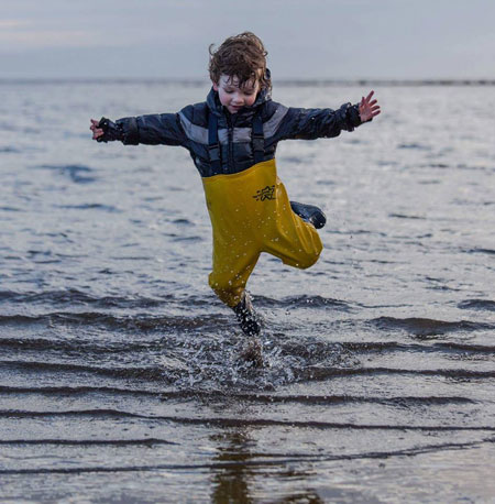Nicki's son having a ball in his waders on a Scottish beach